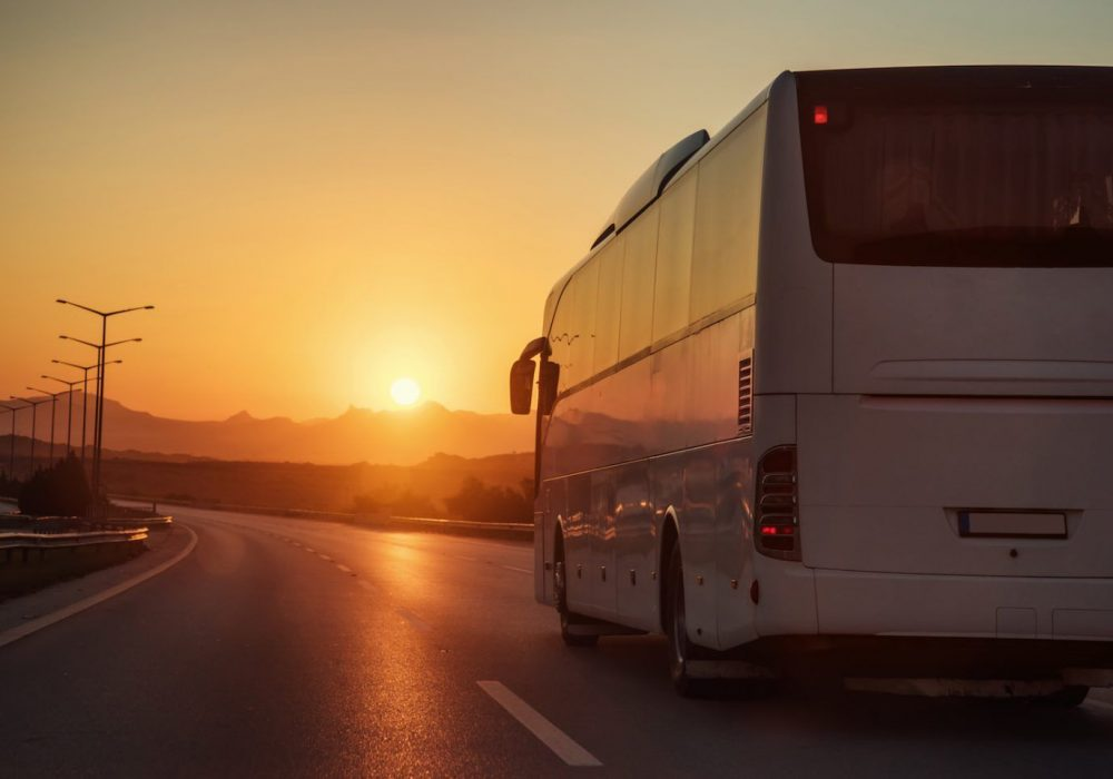 White bus driving on road towards the setting sun